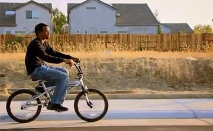 Blind boy riding his bike down the sidewalk